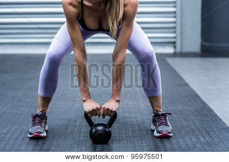Squatting muscular woman lifting kettlebells at the crossfit gym