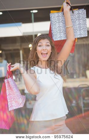 Portrait of euphoric woman raising shopping bags at the shopping mall