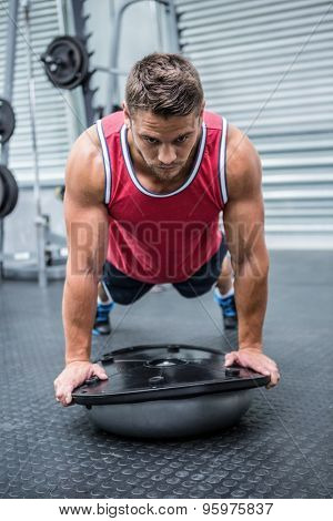 Muscular man using bosu ball in crossfit gym