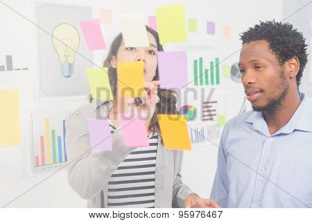 Young creative business people in the office looking at sticky notes