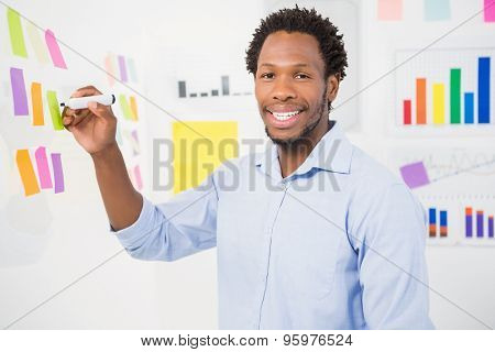 Young smiling businessman writing on sticky notes in the office facing towards the camera