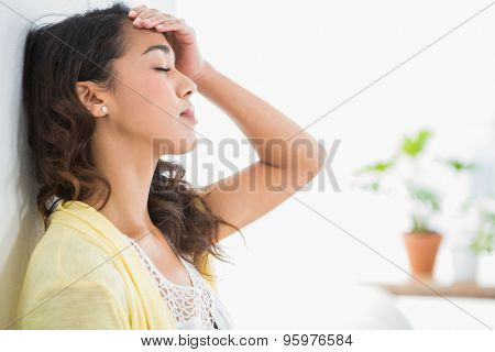 Young thinking businesswoman leaning against a wall in the office with plants in the background
