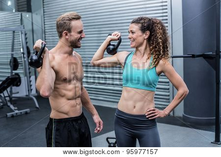 Muscular couple discussing together while lifting kettlebells