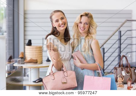 Two beautiful women smiling at camera in shopping mall