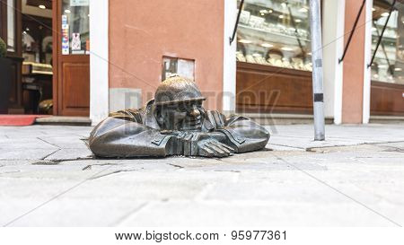 Bratislava, Slovakia - May 07 2013: Cumil  famous statue of man peeking out from under a manhole cov