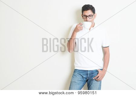 Indian guy drinking coffee. Asian standing on plain background with shadow and copy space. Handsome male model.
