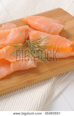 slices of smoked salmon on wooden cutting board and white place mat