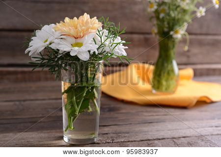 Beautiful flowers in vases on table close up
