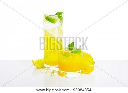 Glasses of lemon juice drink   on white background