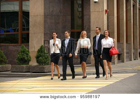 Full length portrait of a young Five successful business people crossing the street in the city center