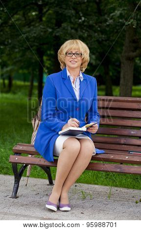 Mature business blonde woman in a jacket with diary sitting on a bench in a summer park