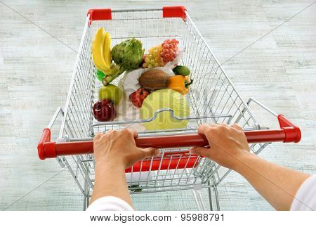 Young woman with shopping cart in store