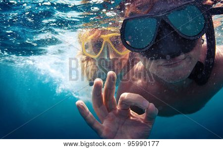 Young couple having fun underwater and showing ok sign