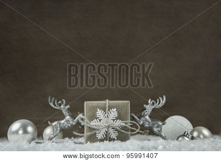 Old wooden background with white and silver grey christmas decoration with gift and moose.