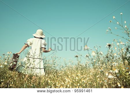 Girl on the way to her future walking in a flowery meadow with her suitcase.