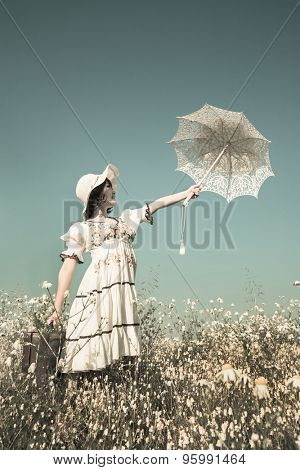 Happy young girl in country style dress stretching her hand with parasol in the sky. Background with shabby chic charm.