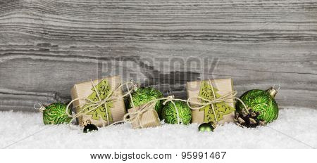 Christmas presents and green balls on wooden old grey background with snow for decorations.
