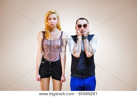 Beautiful young couple standing near looking very amazed and surprised on background