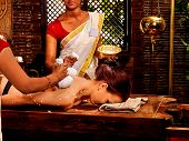 picture of panchakarma  - Woman and two masseuses having Indian massage with pouch of rice - JPG