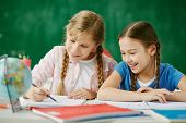 stock photo of schoolgirls  - Two cute schoolgirls drawing together at lesson - JPG