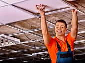 picture of millwright  - Man in builder uniform hand up  installing suspended ceiling - JPG