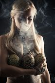 stock photo of woman dragon  - attractive blond with three dragon eggs isolated on black background - JPG