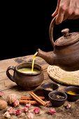 stock photo of darjeeling  - Pouring masala tea from dark ceramic pot - JPG