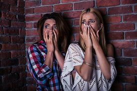 pic of horrifying  - Two scared woman standing with brick wall on background - JPG