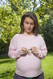 picture of pacifier  - pregnant young woman pink jersey with green pacifier in her hands and green trees background - JPG