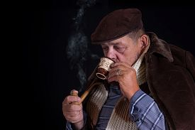 picture of tobacco-pipe  - Senior man being chilled to the bone drinks coffee and smokes tobacco-pipe in the darkness