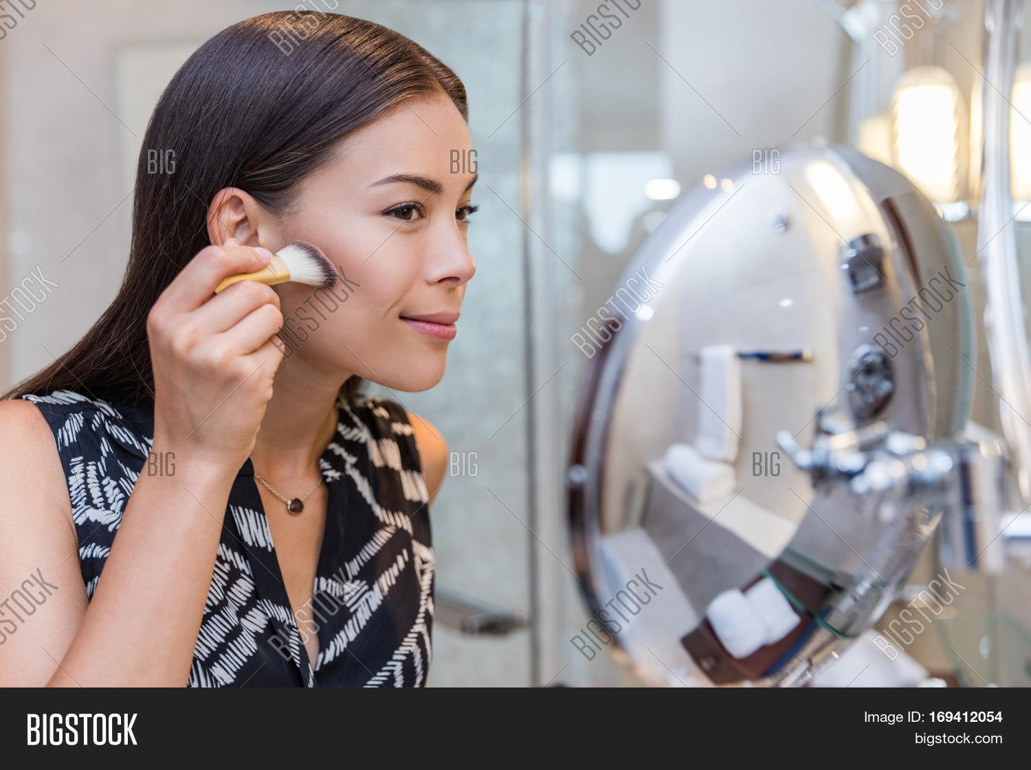 Asian Woman Putting Makeup In Home Bathroom Using A Contour Brush To Apply  Bronzer Powder Under