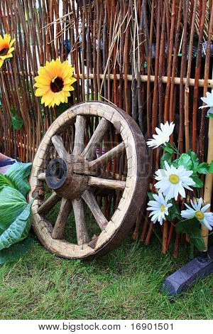 wooden wheel near fence