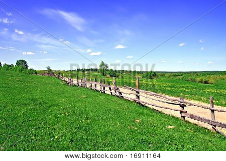 old fence on field along road