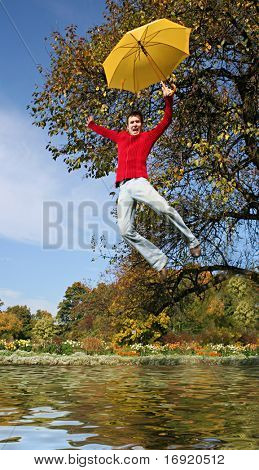 funny guy is flying with yellow umbrella above lake