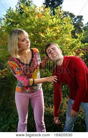strict girl holding guilty guy by the ear