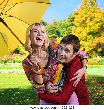 young beautiful couple have fun under yellow umbrella