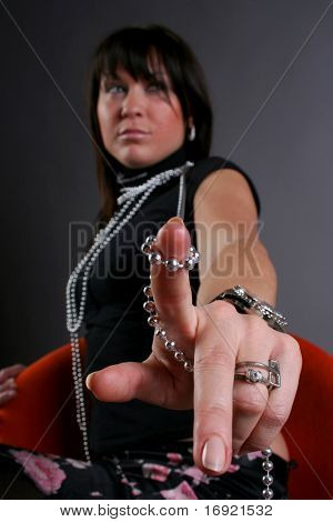 beautiful girl is holding silver beads (hand in focus)