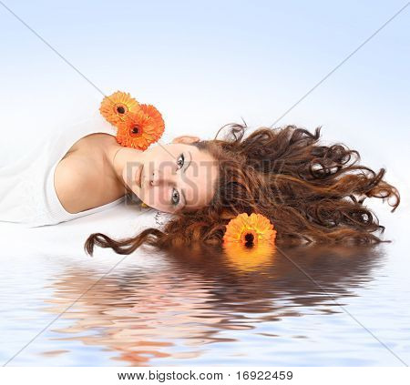 beautiful young girl with flowers is relaxing