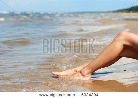 slim girl's legs on sandy beach