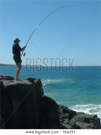 A Fisherman Hooked Into A Fish And Trying To Land It