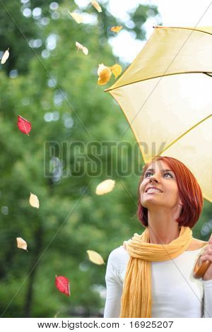 beautiful young girl under yellow umbrella in the autumn park