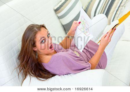 Sorprendido por una mujer bonita sentado en el sofá en casa y con la carta en las manos