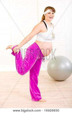 Smiling attractive pregnant woman making gymnastics at home