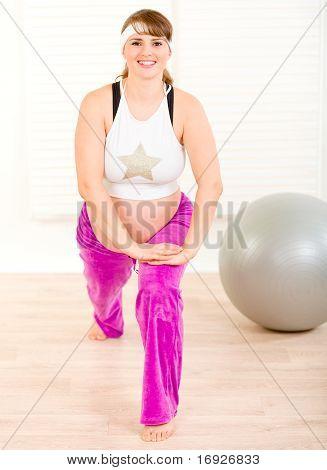 Lächelnd schöne schwangere Frau tun stretching-Übungen