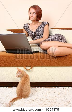 cute young girl relaxing on sofa with laptop