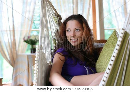 beautiful long-haired girl relaxing in hammock