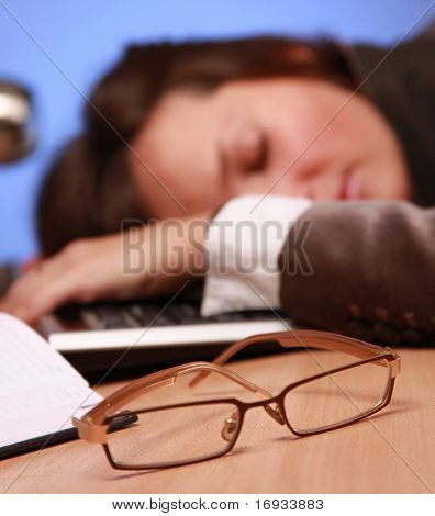 young businesswoman fell asleep at work (glasses in focus )