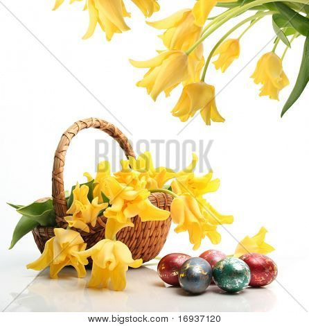 colored easter eggs and yellow tulips in basket