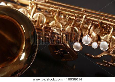 part of shiny golden saxophone on black background