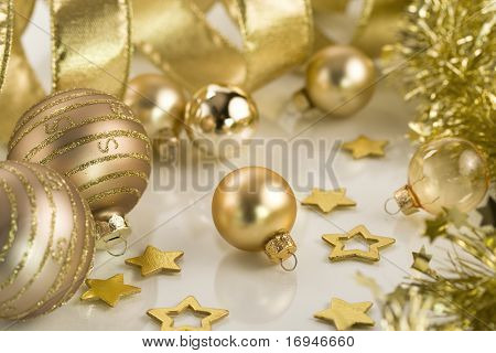 A collection of gold Christmas decorations and tree adornments.